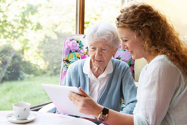 Young caregiver showing something on digital tablet to with 90 years old senior woman, sitting in nice conservatory