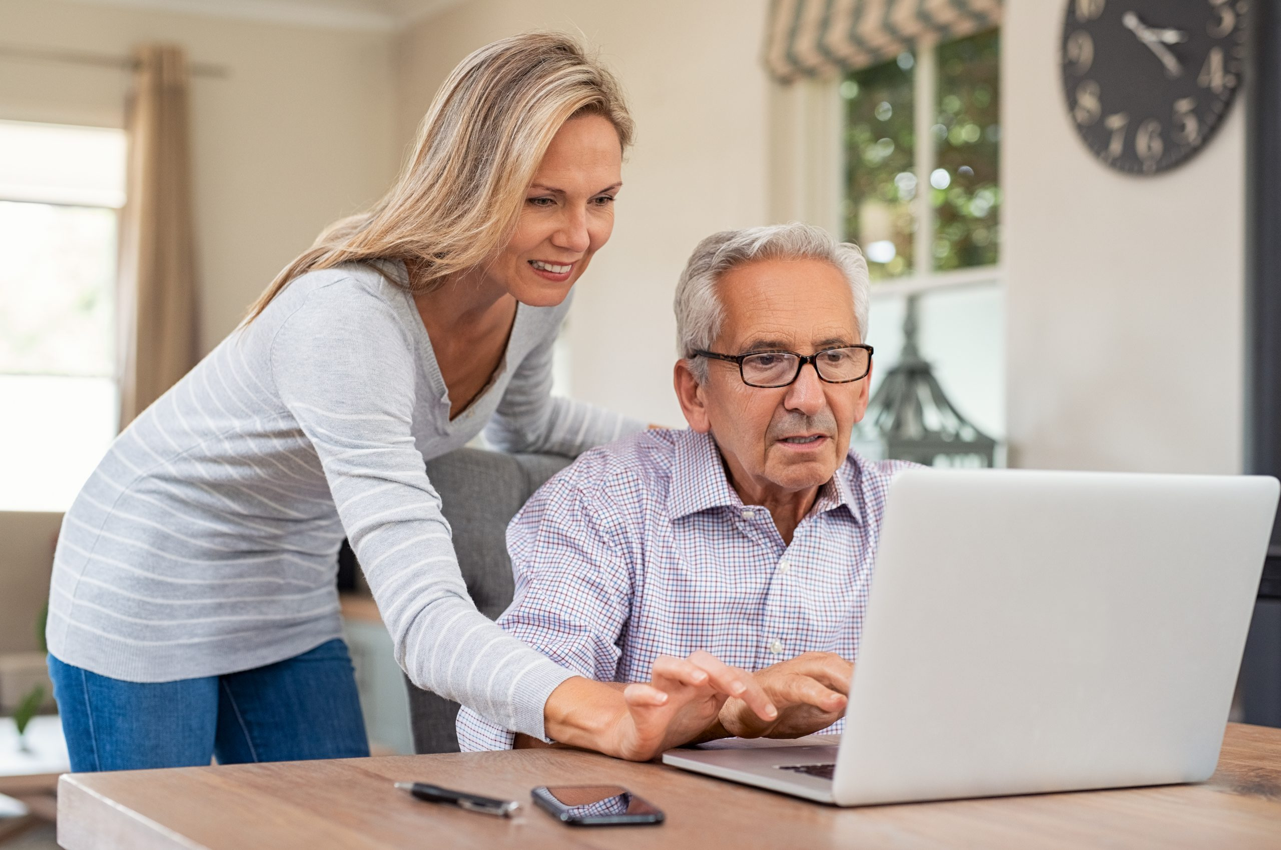 Senior man and mature daughter smiling and looking at laptop at home. Happy daughter teaching and showing new computer technology to her old dfather. Old man learn to use computer.