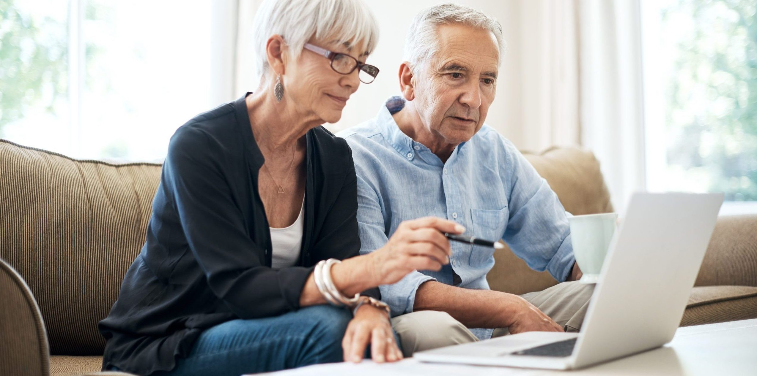 Cropped shot of a senior couple going through their finances while sitting on the sofa at home